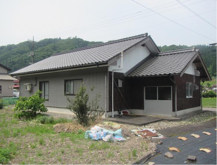 田畑と山に囲まれた場所にある平屋建ての一軒家