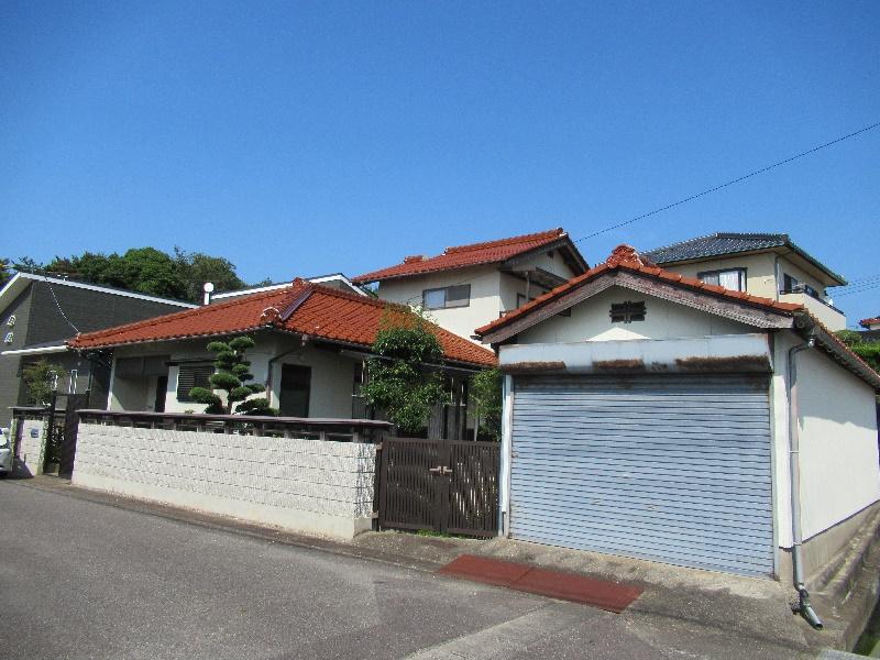 高台の住宅地にある庭付二階建ての一軒家