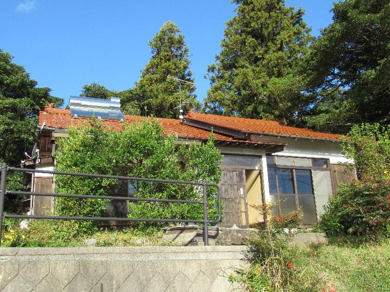 山に囲まれた場所にある平屋建ての一軒家